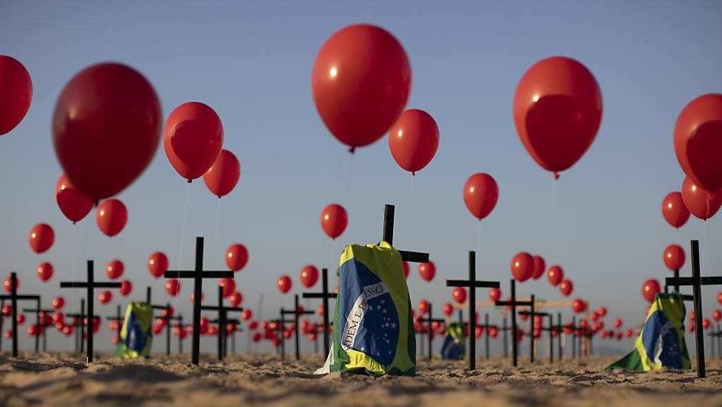 Die Nichtregierungsorganisation «Rio de Paz» platzierte zum Gedenken der Opfer der Covid-19-Pandemie 1000 rote Luftballons und 100 Kreuze am Strand der Copacabana. Die Zahl der Todesopfer des Coronavirus ist in Brasilien auf mehr als 100 000 gestiegen. Foto: Fernando Souza/dpa