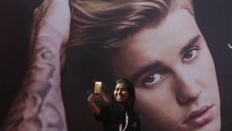 Auch in Indien ein Superstar: Ein indischer Fan macht ein Selfie vor dem überlebensgrossen Plakat des kanadischen Sängers Justin Bieber.