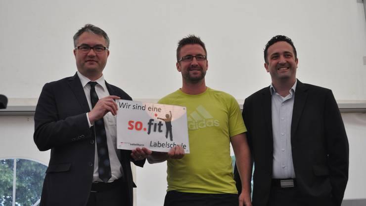 Remo Ankli übergibt das Label so.fit. an den neuen Schulsportleiter Oliver Niklaus und den Hauptschulleiter Martin Müller.
