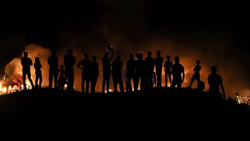 Palästinensische Demonstranten werfen ein brennendes Projektil in Richtung der israelischen Streitkräfte während einer Demonstration östlich von Gaza-Stadt, um gegen den Flaggenmarsch israelischer Nationalisten in Jerusalems Altstadt zu protestieren. Foto: Naaman Omar/APA Images via ZUMA Wire/dpa