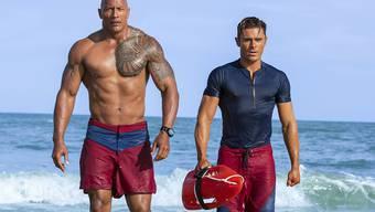 """Dwayne Johnson (l) und Zac Efron (r) haben als """"Baywatch""""-Bademeister am Wochenende die Massen in die Deutschschweizer Kinos gelockt. (Archivbild)"""
