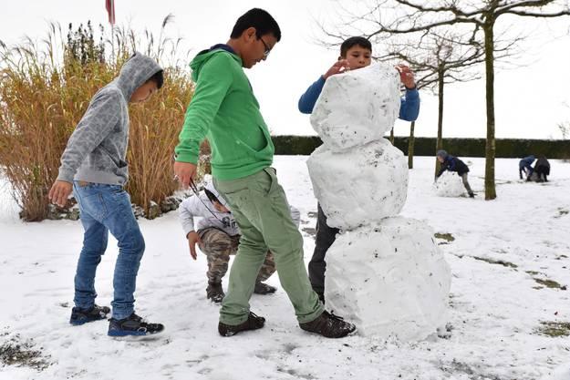 Die Kinder bauen einen grossen Schneemann