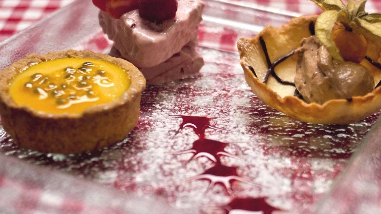 Desserttrilogie aus Tarte au fruit de passion, Tobleronemousse und Erdbeer-Himbeerrahmgefrorenes