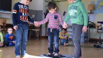 Der Junge in der Mitte hat noch Bedenken, seine Mitschüler helfen ihm.