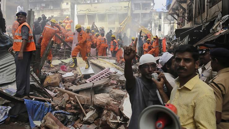 Helfer in den Trümmern des zusammenstürzten Hauses