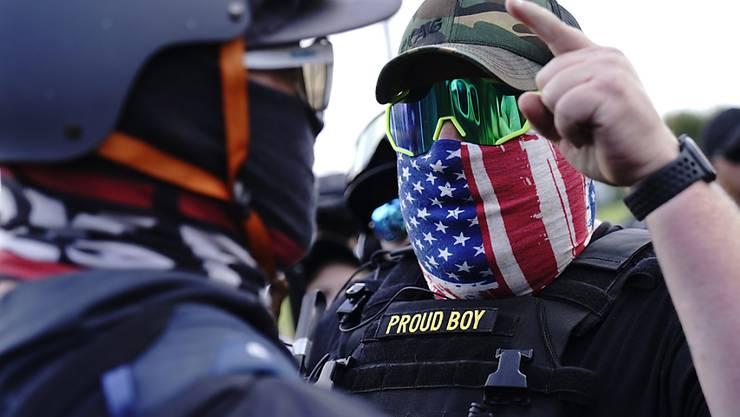 ARCHIV - Ein rechter Demonstrant der Proud Boys (r) diskutiert mit einem Gegendemonstranten, während einer Kundgebung. Foto: John Locher/AP/dpa