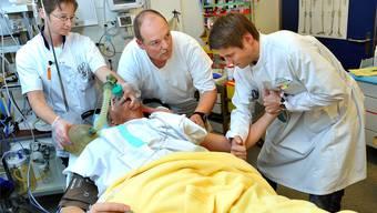 Ein Assistenzarzt renkt unter Aufsicht eines Arztes einem Patienten die Schulter ein.Peter Mosimann/EQ Images