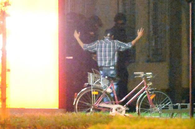 Ein Mann verlässt mit erhobenen Händen den Imbiss-Stand.