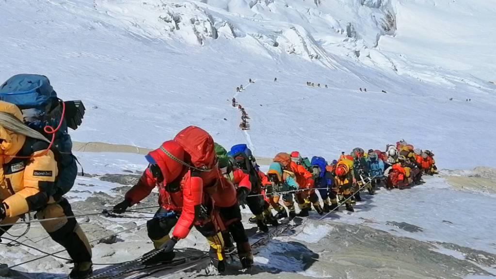 In einer langer Schlange klettern Bergsteiger auf einem Pfad knapp unterhalb von Lager vier. Foto: Rizza Alee/AP/dpa