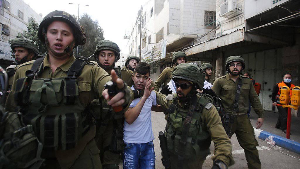 Israelische Soldaten nehmen in der Stadt Hebron im besetzten Westjordanland einen palästinensischen Knaben fest.
