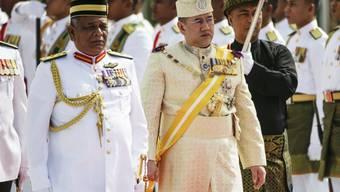 Der neu gekrönte König Sultan Muhammad V. wird während der Willkommenszeremonie durch eine Ehrengarde geführt.