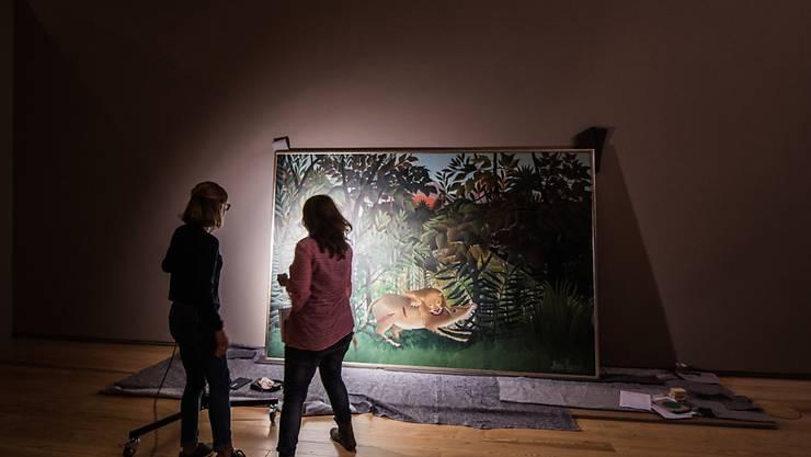 Zwei Restauratorinnen begutachten das Kunstwerk «Der hungrige Loewe wirft sich auf die Antilope» von Henri Rousseau: Das Bild war von Basel nach Frankfurt gereist und wird dort bis 3. Februar zu sehen sein