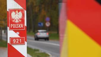 Autos fahren an den Grenzpfählen von Deutschland und Polen vorbei über den Grenzübergang auf der Insel Usedom. Die Bundesregierung hatte Polen ab dem 24.10.2020 als Corona-Risikogebiet eingestuft. Foto: Stefan Sauer/dpa-Zentralbild/dpa