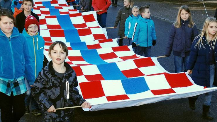 Die Tegerfelder Jugend trägt den 16 Meter langen Schal durch das Dorf.