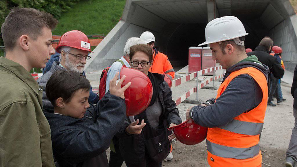 Besucher mit Schutzhelmen machen sich am Tunnelportal des Ceneri-Basistunnels bereit für die Besichtigung.