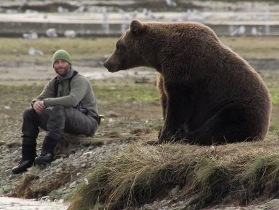 David Bittner setzt oder kniet sich hin und lässt die Bären zu sich kommen.