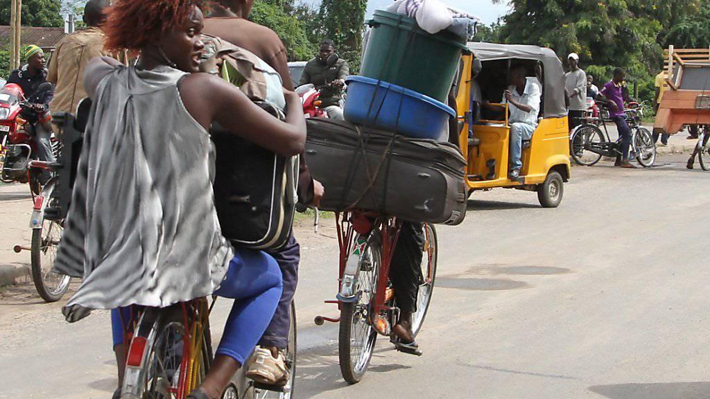 Oft auf Fahrrädern verlassen viele Menschen mit ihrer Habe Burundis Hauptstadt Bujumbura.
