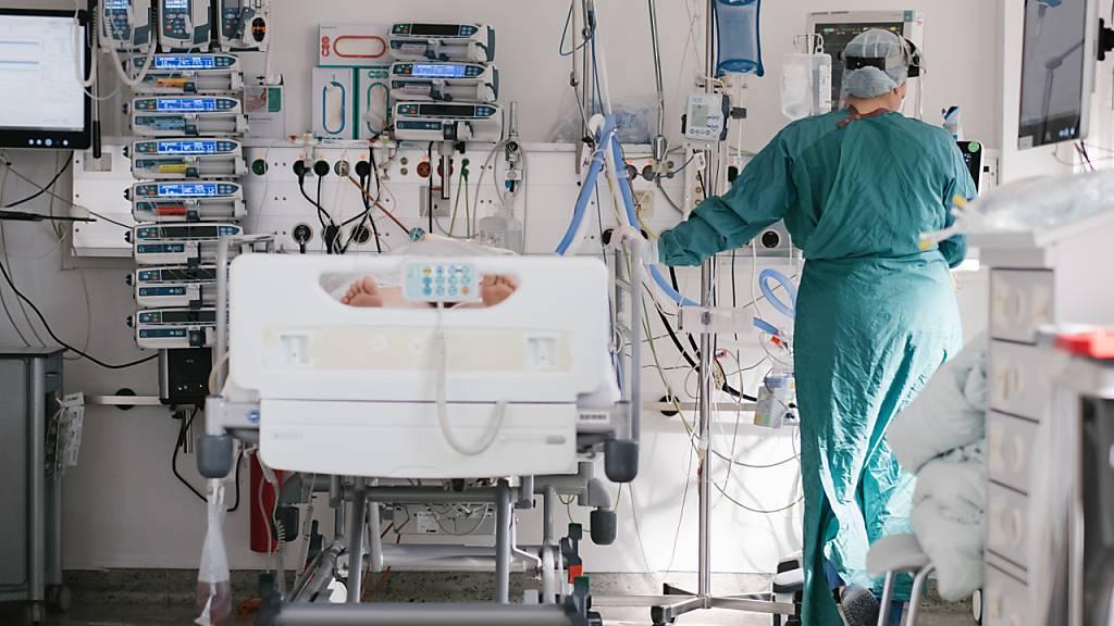 ARCHIV - Eine Intensivpflegerin versorgt auf der Intensivstation am Klinikum Braunschweig einen an Covid-19 erkrankten Patienten. Foto: Ole Spata/dpa