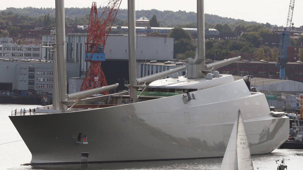 Die Segeljacht «Sailing Yacht A», wie sie am 16. September 2016 in Kiel für ein kurzes Wendemanöver aus dem Dock der Werft von Nobiskrug geschleppt wird, während ein Segelboot vorbeifährt.