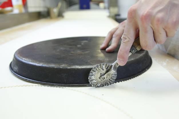 Mit Hilfe eines Kuchenblechs wird der Teig kreisförmig ausgeschnitten
