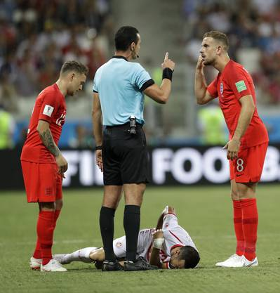 A referee points while speaking to England's Jordan Henderson as Tunisia's Ali Maaloul lies on the field during the group G match between Tunisia and England at the 2018 soccer World Cup in the Volgograd Arena in Volgograd, Russia, Monday, June 18, 2018. (AP Photo/Sergei Grits)