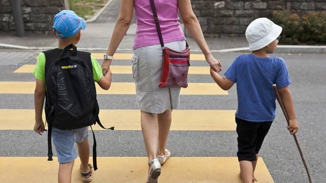 Eine Mutter überquert mit ihren zwei Söhnen einen Fussgängerstreifen (Symbolbild)