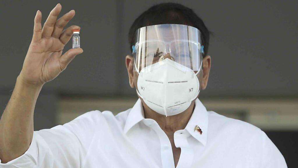 Rodrigo Duterte, Präsident der Philippinen, hält  eine Ampulle mit dem Sinovac-Impfstoff aus China, nachdem der Impfstoff auf der Villamor Air Base eingetroffen ist.
