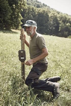 Der Luchsverantwortliche Hans Wampfler inspiziert in Büsserach eine Fotofalle.
