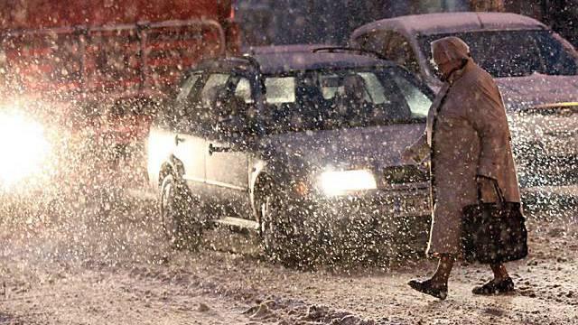 Eine ältere Dame überquert im verschneiten Hamburg die Strasse