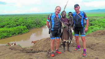 Jörg Peltzer (l.) und Christoph Dietrich in Velokleidung mit äthiopischen Dorfbewohnern.