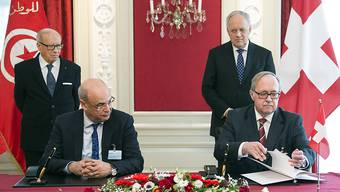 Alt Bundesrat Samuel Schmid (v.r.) und der ehemalige tunesische Wirtschaftsminister Hakim Ben Hammouda (v.l.) unterschreiben das Dokument zur Gründung der Freundschaftsgruppe. Flankiert werden sie dabei von Bundespräsident Johann Schneider-Ammann (h.l.) und Tunesiens Präsident Béji Caïd Essebsi.