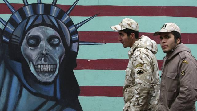 Zwei iranische Soldaten gehen an einem Wandgemälde vorbei (Symbolbild)
