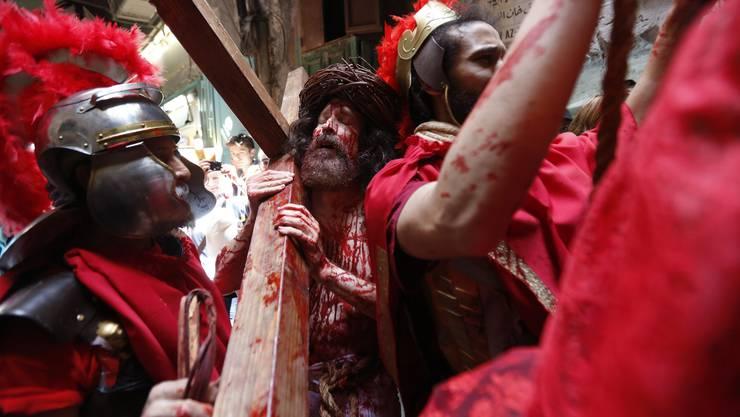 Heilige Woche in Israel: Ein Schauspieler trägt als Jesus das Kreuz durch die Via Dolorosa.