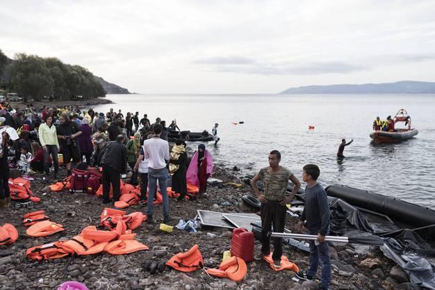Helfer und Flüchtlinge am Strand