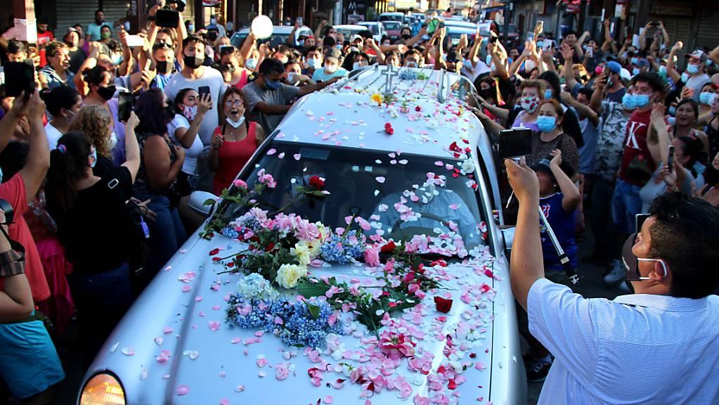 Zahlreiche Menschen mit und ohne Maske begleiten den Leichenwagen mit den sterblichen Überresten von Francisco Martinez, eines Straßenkünstlers, der aufgrund tödlicher Schüsse eines Polizisten gestorben ist. Foto: Agenciauno/Agencia Uno/dpa