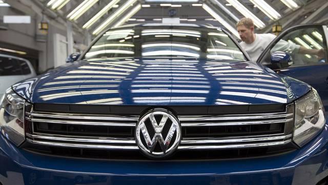 Ein Arbeiter kontrolliert einen VW Tiguan in Wolfsburg (Archiv)