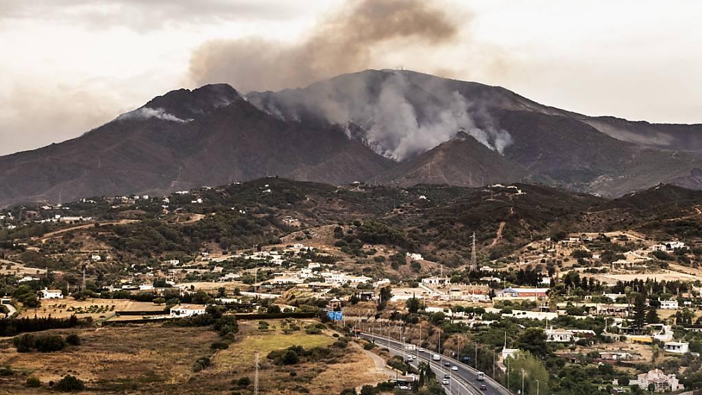 Rauch steigt über Bergen in der Nähe der Stadt Jubrique in der Provinz Malaga auf. Ein verheerender Waldbrand im Süden Spaniens ist nach knapp sechs Tagen unter Kontrolle. Die seit vorigem Mittwoch lodernden Flammen haben unweit der Küstengemeinde Estepona wohl ca. 9700 Hektar Wald zerstört. Foto: Pedro Armestre/AP/dpa