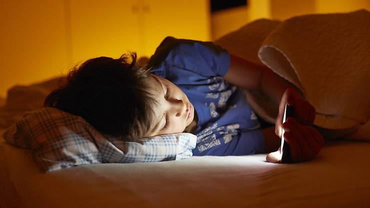 Der abendliche Blick auf das Handydisplay kann die Ausschüttung des schlafanstossenden Hormons Melatonin verzögern. Jugendliche sind deshalb oft nicht genügend ausgeruht. (Symbolbild)