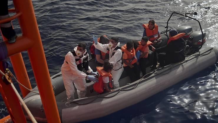 """Maltesische Soldaten helfen Flüchtlingskindern, von der """"Ocean Viking"""" auf ihre Rettungsboot umzusteigen."""