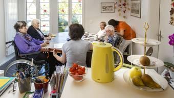 Im Esszimmer kommen die WG-Bewohnerinnen zusammen. Einmal in der Woche besucht sie eine Aktivierungstherapeutin (am Kopf des Tisches). Eine Pflegerin (ganz rechts) ist rund um die Uhr vor Ort.
