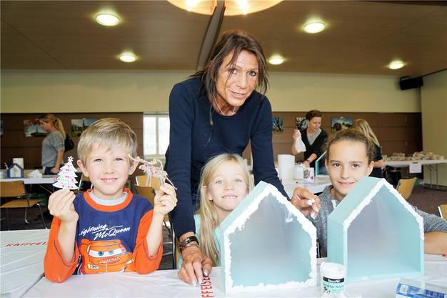 Karin Gallati (59) aus Reinach unterstützt ihre Grosskinder Sandro (5), Alina (7) und Leonie (11) beim Verzieren von Weihnachtsschmuck und beim Basteln von Häuschen, die mit LED-Lämpchen beleuchtet werden.