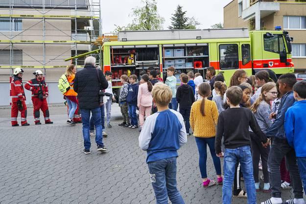 Die Kinder schauen sich nach erfolgreicher Evakuation das Feuerwehrauto an.