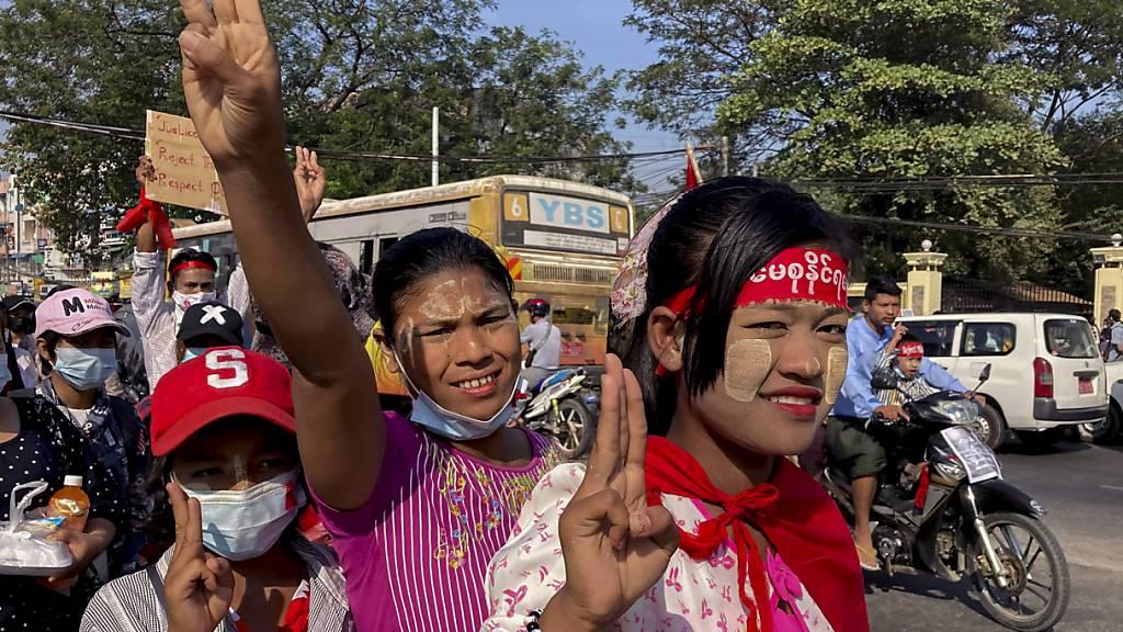 Demonstranten machen den Dreifingergruß als Symbol des Widerstandes gegen den Militärputsch. Ungeachtet internationaler Appelle, Sanktionen und Großdemonstrationen geht die neue Militärjunta in Myanmar weiter hart gegen die entmachtete zivile Regierung vor. Foto: Str/AP/dpa