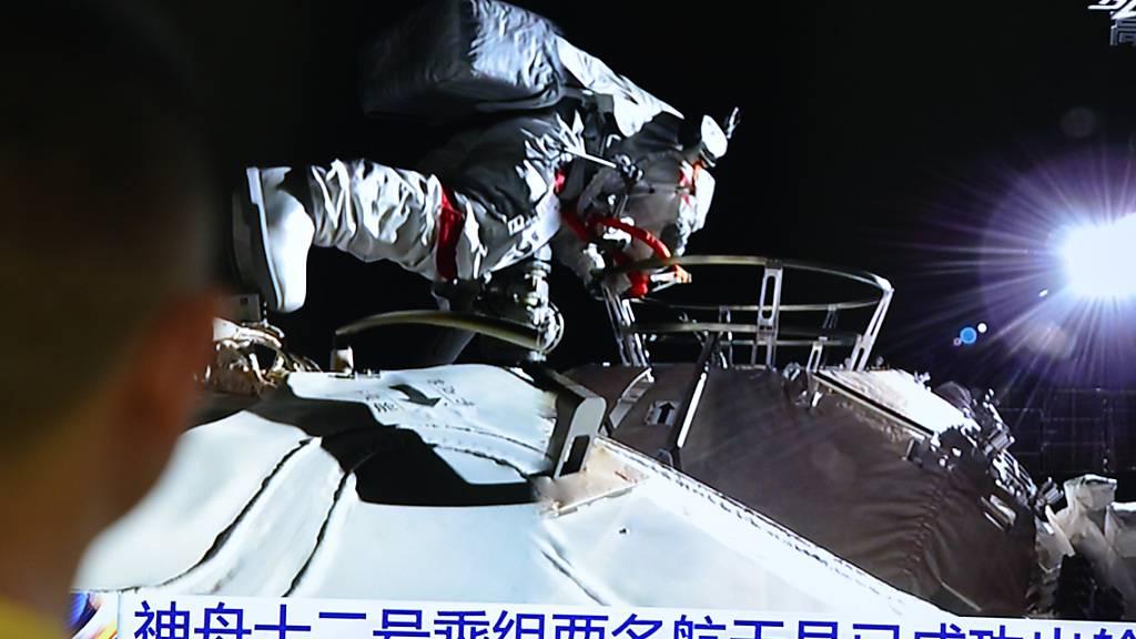 ARCHIV - Ein Mann verfolgt die Live-Übertragung über Astronauten des chinesischen Raumschiffs «Shenzhou 12», die in ihren Raumanzügen die Station verlassen 04.07.2021). Die drei Astronauten sind nach der Mission wieder auf der Erde gelandet. Foto: Sheldon cooper/SOPA Images via ZUMA Wire/dpa