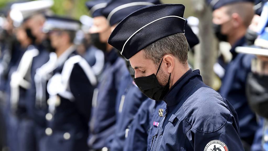 Ein Polizist hat seine Augen geschlossen und neigt seinen Kopf während einer Zeremonie zu Ehren des Polizisten Eric Masson. Masson wurde an einem Drogenumschlagplatz in Avignon getötet. Foto: Nicolas Tucat/POOL AFP/AP/dpa