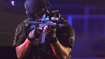 Ein US-Polizist hält seine Waffe im Anschlag (Archiv)