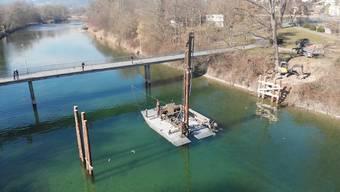 Am Montagabend ist das Floss für den Rammbagger vorbereitet worden, am Dienstag sind die ersten Holzpfähle in den Flussgrund gerammt worden.