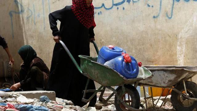 Eine Frau transportiert in Sanaa zwei mit Wasser gefüllte Kanister