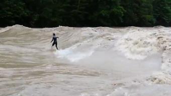 Waghalsiger geht bei Hochwasser auf der Thur surfen.