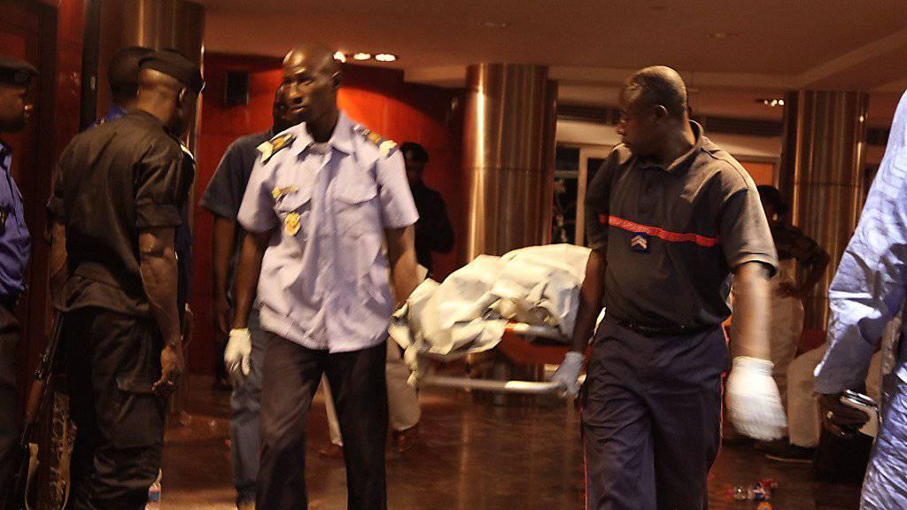 Sicherheitskräfte bergen die Leiche eines der 21 Opfer der Geiselnahme in Mali.